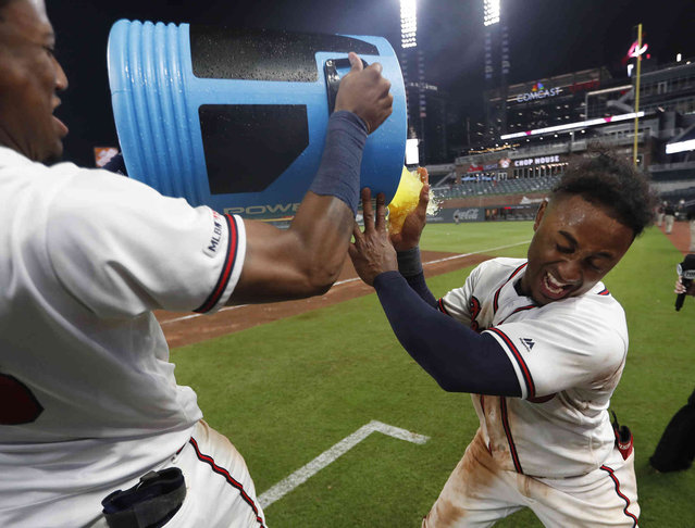 Atlanta Braves' Ozzie Albies, right, is doused by Ronald Acuna Jr., after driving in the winning run with a double in the 11th inning of a baseball game against the Pittsburgh Pirates early Thursday, June 13, 2019, in Atlanta. The Braves won 8-7. (Photo by John Bazemore/AP Photo)