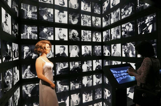 """A visitor looks at a wax figure of Italian Actress Sofia Loren with other actor's portraits during a media tour of """"Chaplin's World"""", an interactive museum celebrating the life and works of comic actor Charlie Chaplin, in Corsier near Vevey, Switzerland, April 16, 2016. The museum is set on the vast estate of Manoir de Ban, where Chaplin spent the last 25 years of his life until his death. (Photo by Denis Balibouse/Reuters)"""