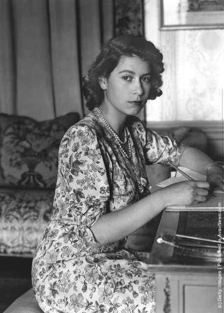 1944: Queen Elizabeth II (as Princess Elizabeth) writing at her desk in Windsor Castle, Berkshire