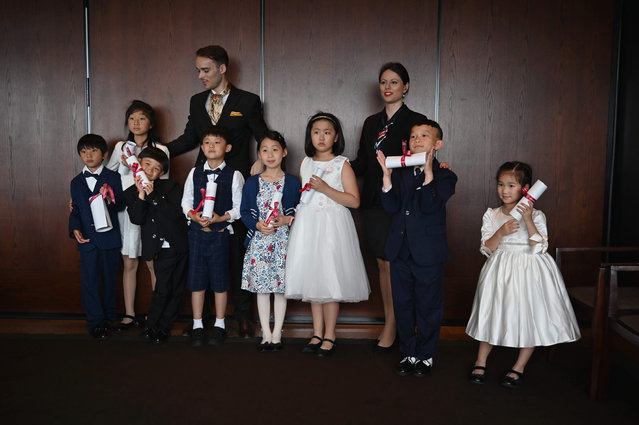 This picture taken on June 1, 2019 shows Guillaume de Bernadac (back L) and Miona Milakov (back R) posing for photographs with children after an etiquette and manners class in central Shanghai. (Photo by Hector Retamal/AFP Photo)