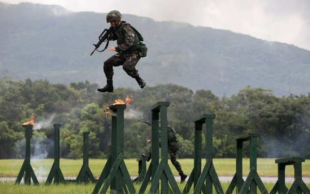 A soldier of the Peoples' Liberation Army (PLA) performs drills during a demonstration at an open day at the Ngong Shuen Chau Barracks in Hong Kong on June 30, 2019, to mark the 22nd anniversary of Hong Kong's handover from Britain to China on July 1. (Photo by Paul Yeung/Bloomberg)