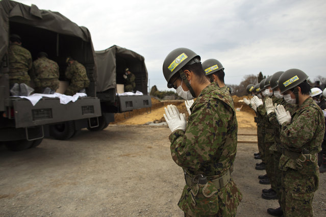 Japan Self-Defense Force members pay their respect to unidentified earthquake victims in vehicles during a mess funeral on April 8, 2011 in Yamamoto, Miyagi Prefecture, Japan. The 9.0 magnitude strong earthquake struck offshore on March 11 at 2:46pm local time, triggering a tsunami wave of up to ten metres which engulfed large parts of north-eastern Japan, and also damaging the Fukushima nuclear plant and threatening a nuclear catastrophe. The death toll continues to rise with numbers of dead and missing exceeding 20,000 in a tragedy not seen since World War II in Japan.  (Photo by Athit Perawongmetha/Getty Images)