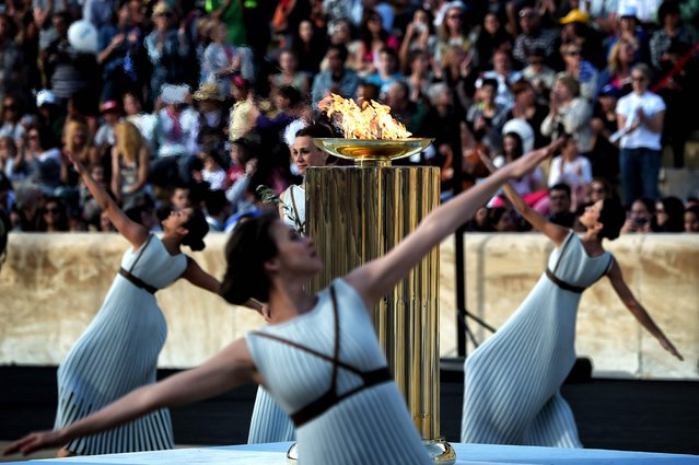 Priestesses dance around the Olympic flame burning in a cauldron, during the handover ceremony at thePanathinean stadium in Athens, on April 27, 2016. Greece on April 27 handed over to Brazilian officials the Olympic flame of the Rio Games as the 100-day countdown to the August 5 opening ceremony begins. (Photo by Aris Messinis/AFP Photo)