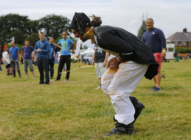 A competitor in fancy dress fails to make a clean catch during the World Egg Throwing Championships and Vintage Day in Swaton, Britain June 28, 2015. (Photo by Darren Staples/Reuters)