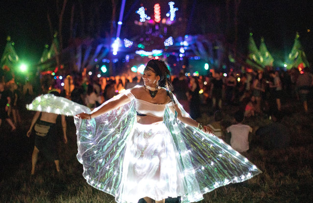 """A reveler dances during the seven-day O.Z.O.R.A. Festival, described by organizers as a """"psychedelic tribal gathering"""", near the village of Ozora, Hungary, 31 July 2019 (issued 01 August 2019). Organizers say the visitors are connected by the love of psychedelic music as well as the love of environment, and also by the emotional intelligence and the spiritual sensitivity. The first gathering was held in 1999, when the total solar eclipse could be observed from Hungary. The festival is a meeting point of psychedelic music and ancient transcendental cultures, thus visitors can enjoy products of fine arts, theatre, underground circus besides music, and lectures on esoteric, scientific or philosophical topics. Workshops are also held in various fields of handicrafts for those who wish to trained in these skills. (Photo by Balazs Mohai/EPA/EFE)"""