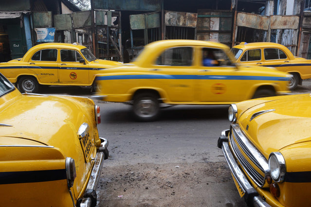 In this photograph taken on February 14, 2017, Indian Hindustan Motors Ambassador taxis stand parked on a street in Kolkata India' s Hindustan Motors has sold its Ambassador car to France' s Peugeot for just USD12 million, capping a spectacular downfall for a vehicle once emblematic of the country' s political class. The CK Birla group, the owners of Hindustan Motors, have sold the car brand for 800 million rupees to the French auto makers, a company spokesman confirmed to AFP. Hindustan Motors, India' s oldest car maker, stopped production of the Ambassador in 2014 citing debt and lack of demand for the vehicle which was designed on Britain' s long- defunct Morris Oxford. (Photo by Dibyangshu Sarkar/AFP Photo)