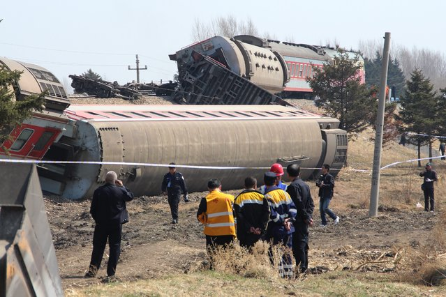 Rescuers and investigators are seen at the site where a train derailed in the Hailun country of Suihua City, northeast China's Heilongjiang province, 13 April 2014. A passenger train which runs from Heihe to Harbin, derailed at the section in Hailun county in the early morning hours of 13 April 2014, causing 15 passengers suffering injuries, according to local media reports. A cause for the accident was not immediately reported.  (Photo by EPA/STR)