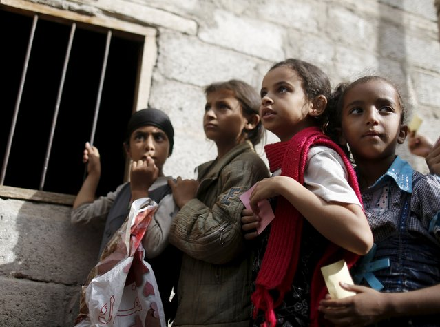Girls wait for food rations outside a charity food assistance center in Yemen's capital Sanaa July 1, 2015. (Photo by Khaled Abdullah/Reuters)