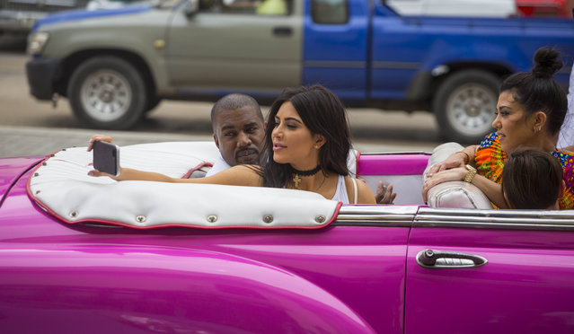 American reality-show star Kim Kardashian takes a selfie as she rides on a classic car next to her husband, rap superstar Kayne West and her sister Kourtney Mary Kardashian in Havana, Cuba, Wednesday, May 4, 2016. West, Kardashian and members of her reality-show-star family have become the latest celebrities to visit Havana. They visited Havana's Museum of Rum Wednesday, stepping out of a hot-pink antique American convertible as they snapped selfies and were recorded by a television crew following them around. (Photo by Desmond Boylan/AP Photo)