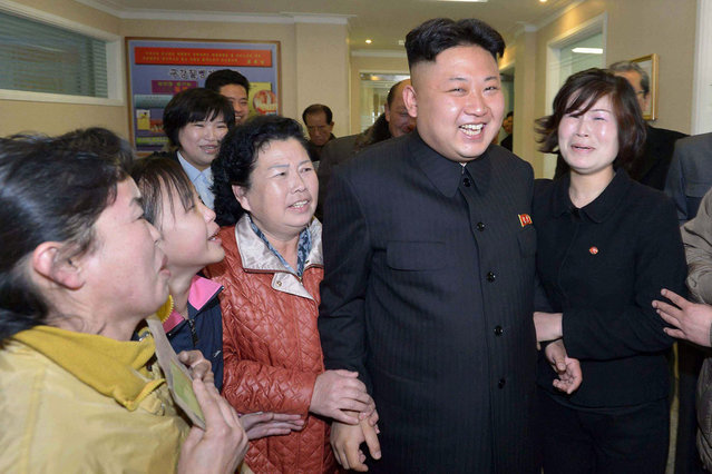 """This undated picture released by North Korea's official Korean Central News Agency (KCNA) on March 22, 2014 shows North Korean leader Kim Jong-Un (C) during a visit to the Ryugyong Dental Hospital in Pyongyang. Meanwhile, North Korea test-fired 30 short-range missiles into the sea on March 22, South Korea's Joint Chiefs of Staff said, the latest in a series of launches despite calls from Seoul and Washington to stop """"provocative actions"""". (Photo by AFP Photo/KCNA via KNS)"""