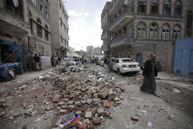 People inspect the site of an airstrike by Saudi-led coalition forces, in Sanaa, Yemen, Thursday, May, 16, 2019. Yemen's human rights minister says heavy fighting is underway in the country's south as rebel Houthis push to gain more territory from government forces and their allies. The clashes come as the Saudi-led coalition carried out airstrikes on the capital, Sanaa, earlier on Thursday, targeting the Houthis and killing at least three civilians. (Photo by Hani Mohammed/AP Photo)