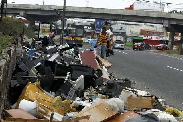 People walk near garbage at the entrance to the neighbourhood La Chorotega, where health workers perform fumigation to help control the spread of the mosquito-borne Zika virus, after health authorities reported cases of the virus in San Jose, Costa Rica May 6, 2016. (Photo by Juan Carlos Ulate/Reuters)