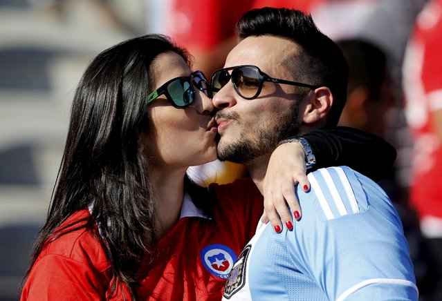 A Chile fan (L) kisses an Argentina fan as they await the start of the teams' Copa America 2015 final soccer match at the National Stadium in Santiago, Chile, July 4, 2015. (Photo by Jorge Adorno/Reuters)
