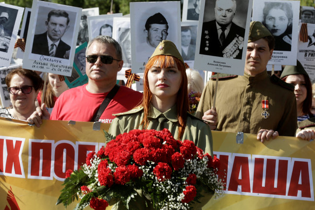 People hold pictures of World War Two soldiers as they take part in the Immortal Regiment march during the Victory Day celebrations in Riga, Latvia May 9, 2016. (Photo by Ints Kalnins/Reuters)