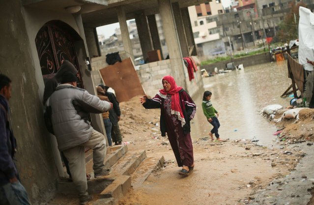 A Palestinian woman asks for help after her house was flooded following heavy rain in a neighbourhood in the northern Gaza Strip February 16, 2017. (Photo by Mohammed Salem/Reuters)