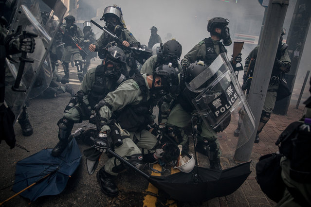 """Police tackle and arrest pro-democracy protesters during clashes in Wan Chai on October 01, 2019 in Hong Kong, China. Pro-democracy protesters marked the 70th anniversary of the founding of the People's Republic of China in Hong Kong through demonstrations as the city remains on the edge with the anti-government movement entering its fourth month. Protesters in Hong Kong continue its call for Chief Executive Carrie Lam to meet their remaining demands since the controversial extradition bill has been withdrawn, which includes an independent inquiry into police brutality, the retraction of the word """"riot"""" to describe the rallies, and genuine universal suffrage, as the territory faces a leadership crisis. (Photo by Chris McGrath/Getty Images)"""