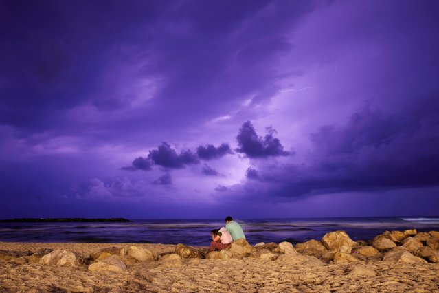 People are seen on the beach as lightning strikes over the Mediterranean at the city of Ashkelon, Israel, March 24, 2019. (Photo by Amir Cohen/Reuters)