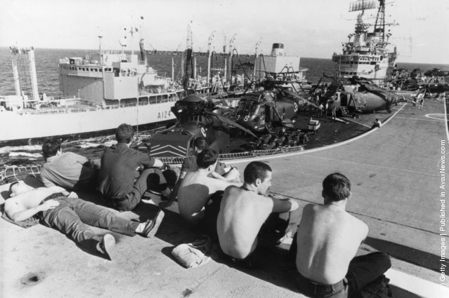 1982: Marines relaxing on the 'ski jump' ramp of HMS Hermes, as she is replenished at sea by a Royal Fleet auxiliary vessel, on the way to the Falkland Islands. Westland Sea King helicopters can be seen on deck
