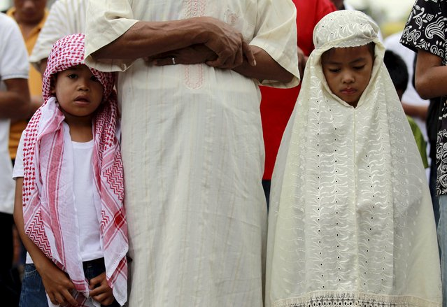 Muslim children offer their morning prayers beside their father at a park in a slum area in Tondo, metro Manila July 17, 2015. (Photo by Romeo Ranoco/Reuters)