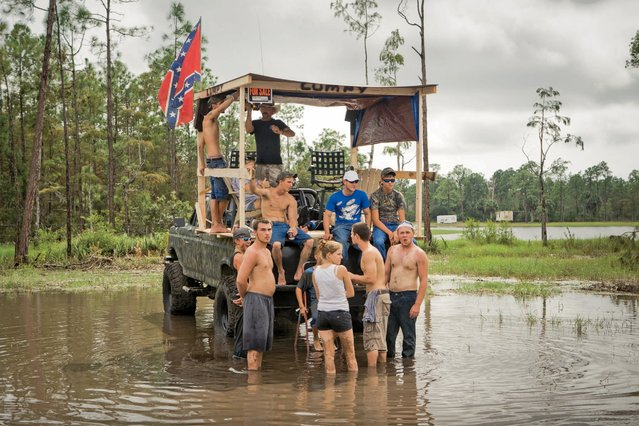 "Local swamp buggy race fans seek refuge from the standing water atop ""Lumpy"", a custom-built platform erected on the back of a truck at the Florida Sports Park. ""She took a half step too far when she went to kick me in the a*s. Needless to say, they swelled like oranges and she started calling me ""Lumpynuts"". In time, it shortened to just ""Lumpy"", Chris Steinmann said. (Photo by Malcolm Lightner)"