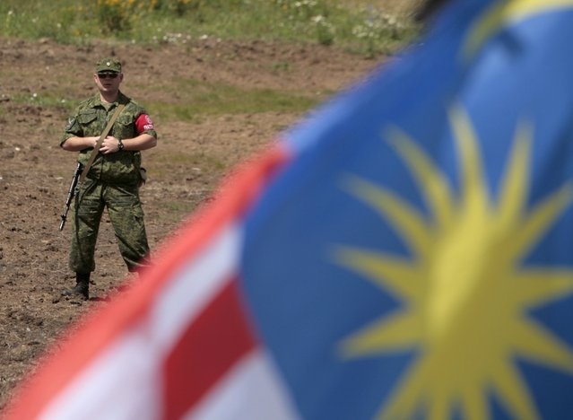 A member of the self-proclaimed Donetsk People's Republic forces stands guard during a commemoration ceremony at the site of the Malaysia Airlines flight MH17 plane crash near the village of Hrabove in Donetsk region, Ukraine, July 17, 2015. (Photo by Kazbek Basaev/Reuters)