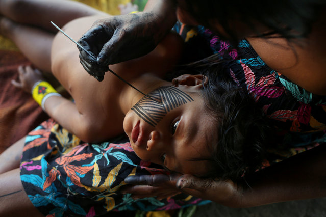 A Kayapo indigenous woman paints her daughter with a Kayapo traditional drawing in Bau village near Novo Progresso, Para state, Brazil on September 14, 2019. (Photo by Amanda Perobelli/Reuters)