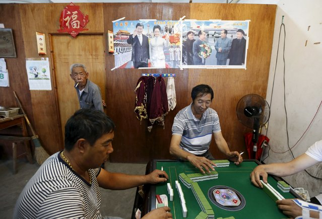People play mahjong in front of a poster of Chinese President Xi Jinping and his wife Peng Liyuan, and a poster of China's former leaders, as Typhoon Chan-Hom approaches southern China, in Wenling, Zhejiang province, July 8, 2015. Chinese authorities have suspended train services, closed schools and bought trawlers back to port before two typhoons in the south and east of the country make landfall later this week, state media said. (Photo by William Hong/Reuters)