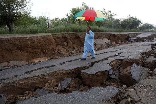 A man walks with an umbrella along a damaged road after an earthquake in Jatlan, Mirpur, Pakistan, September 25, 2019. (Photo by Akhtar Soomro/Reuters)