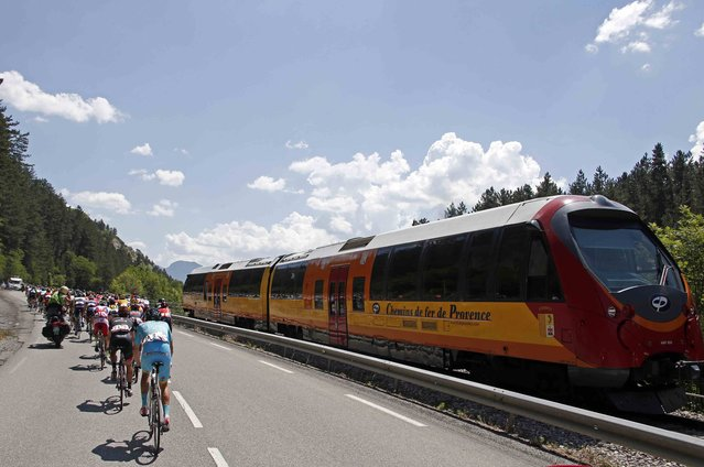 The pack of riders cycle past a train during the 161-km (100 miles) 17th stage of the 102nd Tour de France cycling race from Digne-les-Bains to Pra Loup in the French Alps mountains, France, July 22, 2015. (Photo by Eric Gaillard/Reuters)