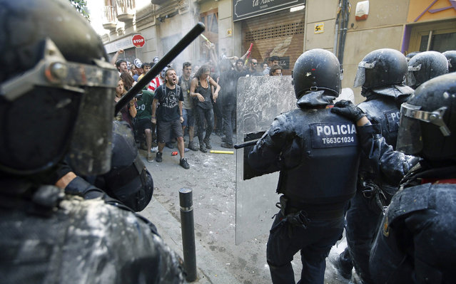 epaselect epa05336277 Demonstartors shout slogans at police during a protest in the surroundings of an occupied old bank branch, which was cleared from squatters last week, in the Gracia neighbourhood, Barcelona, northeastern Spain, 29 May 2016. Police clashed with some 200 demonstrators who took part in the protest against the evictions. The squatters had been living there since 2011. (Photo by Andreeu Dalmau/EPA)