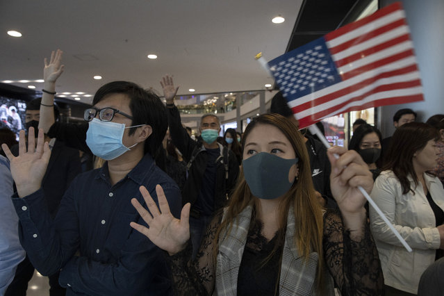 """Hongkongers hold up their hands to represent their five demands and a United States flag as they chant """"Pass the bill, save Hong Kong"""" at the IFC mall in Hong Kong Thursday, November 21, 2019. Pressure ratcheted up on Hong Kong as the U.S. Congress approved legislation late Wednesday to sanction officials who carry out human rights abuses and require an annual review of the favorable trade status that Washington grants Hong Kong. Another bill bans export of tear gas and other non-lethal tools to Hong Kong. (Photo by Ng Han Guan/AP Photo)"""