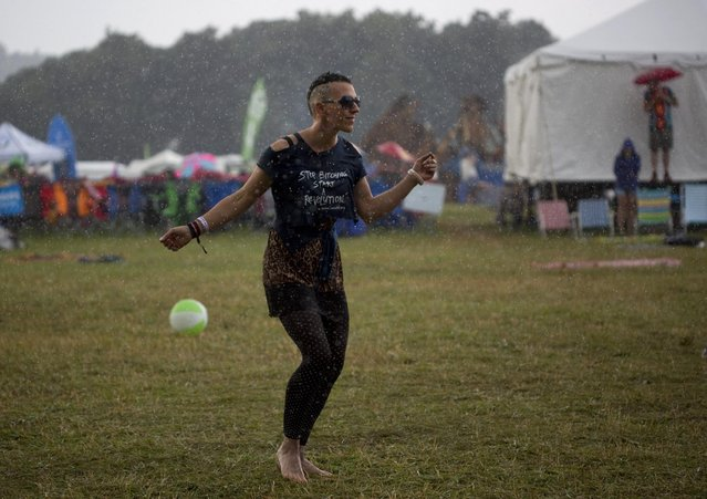 Amber Skies of Floyd, Va., dances in the rain to Rayland Baxter's performance on the Dreaming Creek main stage during Floyd Fest in Floyd, Va., on Saturday, July 25, 2015. A short downpour of rain during their set didn't stop the band from performing. (Photo by Erica Yoon/The Roanoke Times via AP Photo)