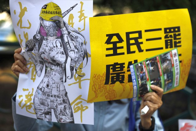 "An anti-government supporter holds up banners during a rally by the advertising industry in Hong Kong on Monday, December 2, 2019. Several hundred people who work in advertising in Hong Kong say they will strike this week to support the anti-government protests in the semi-autonomous Chinese territory. The banner, right, read ""Advertising Industry joins all citizens three boycotts"". (Photo by Vincent Thian/AP Photo)"