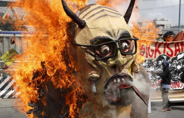 Protesters burn an effigy of President Benigno Aquino during a rally near Batasang Pambansa in Quezon city, Metro Manila in the Philippines, July 27, 2015. Aquino will address the joint session of Congress delivering his last State of the Nation address at the Batasang Pambansa this afternoon. (Photo by Erik De Castro/Reuters)
