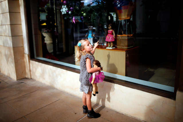 Charli Crosby, 5, points to a doll in the window of an American Girl store at The Grove mall in Los Angeles November 26, 2013. (Photo by Lucy Nicholson/Reuters)