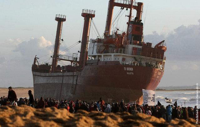Demonstrators and onlookers gather in front of the beached cargo TK Bremen at Erdeven, on December 17, 2011