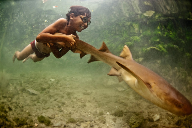 """""""Enal with Pet Shark"""". Whilst many sea nomads have now moved on to land as a result of marine degradation in The Coral Triangle region. Many still retain a magical link with the ocean. Here Enal, a young Bajau boy, rides on the tail of a shark, Wakatobi, Indonesia. July 2010. (Photo by James Morgan)"""