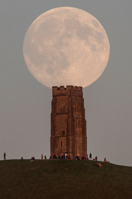 The moon rises over people gathered on Glastonbury Tor ahead of tomorrow's Blue Moon on July 30, 2015 in Somerset, England. (Photo by Matt Cardy/Getty Images)