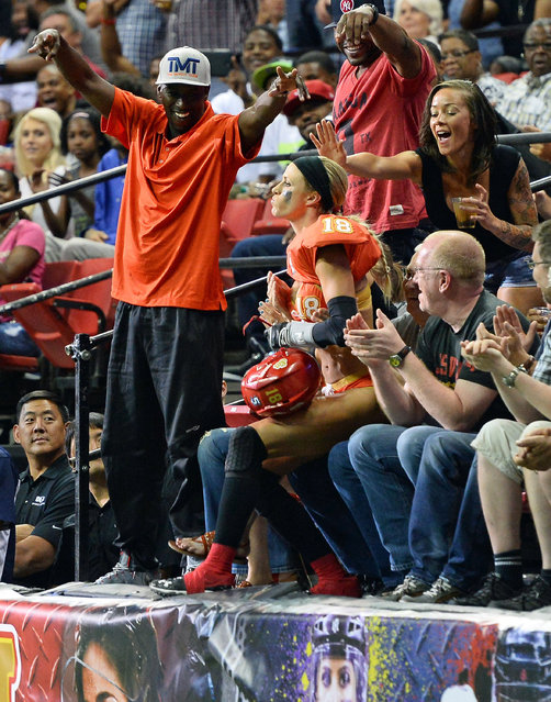 Cynthia Schmidt #18 of the Las Vegas Sin sits on a fan's lap after jumping into the crowd to celebrate scoring a touchdown against the Green Bay Chill during their game at the Thomas & Mack Center on May 15, 2014 in Las Vegas, Nevada. Las Vegas won 34-24. (Photo by Ethan Miller/Getty Images)