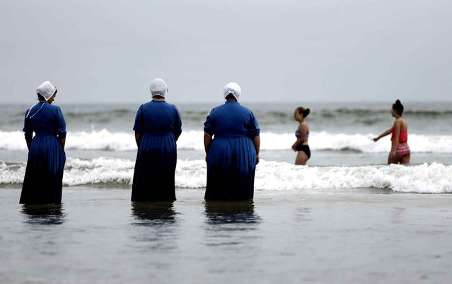 Rosa Graber, third from left, and Margerie, Steury, second from left, Joanne Steury, left, look on as they touch Pacific Ocean waters for the first time during a family trip from their Amish community in Michigan Thursday, June 9, 2016, in Coronado, Calif. (Photo by Gregory Bull/AP Photo)