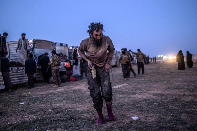 A man suspected of belonging to the Islamic State (IS) group walks past members of the Kurdish-led Syrian Democratic Forces (SDF) just after leaving IS' last holdout of Baghouz, in the eastern Syrian province of Deir Ezzor on March 4, 2019. (Photo by Bulent Kilic/AFP Photo)