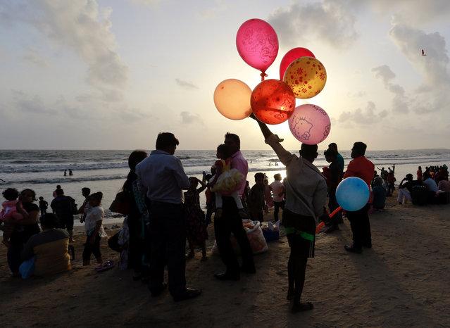 A man sells balloons as people enjoy the beach along the Arabian Sea in Mumbai, June 20, 2017. (Photo by Danish Siddiqui/Reuters)