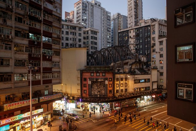 People cross the road outside the State Theatre Building that is slated for demolition in the North Point neighbourhood in Hong Kong, China, December 11, 2019. (Photo by Thomas Peter/Reuters)