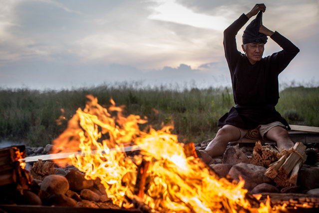 """Cormorant master, Mr. Masahiko Sugiyama puts on his traditional Kazori-Eboshi (hat) around a bonfire prior to the start of the nights Ukai on July 2, 2014 in Gifu, Japan. In this traditional fishing art """"ukai"""", a cormorant master called """"usho"""" manages cormorants to capture ayu or sweetfish. The ushos of River Nagara have been the official staff of the Imperial Household Agency of Japan since 1890. Currently six imperial fishermen of Nagara River conduct special fishing to contribute to the Imperial family eight times a year, on top of daily fishing from mid-May to mid-October. (Photo by Chris McGrath/Getty Images)"""