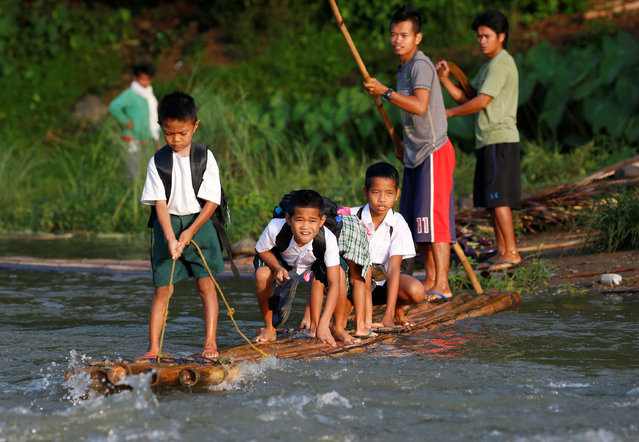 Schoolchildren ride on a makeshift raft to attend the opening of classes at a remote Casili Elementary School in Montalban, Rizal northeast of Manila, Philippines June 13, 2016. (Photo by Erik De Castro/Reuters)
