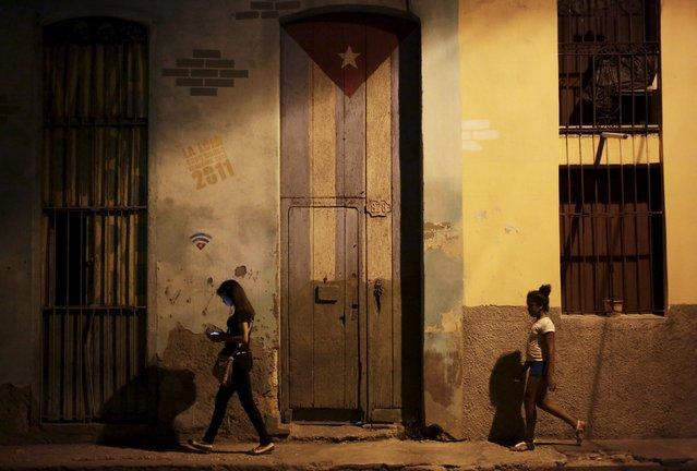 People walk near a door painted with the Cuban flag, in Havana April 10, 2015. (Photo by Enrique De La Osa/Reuters)