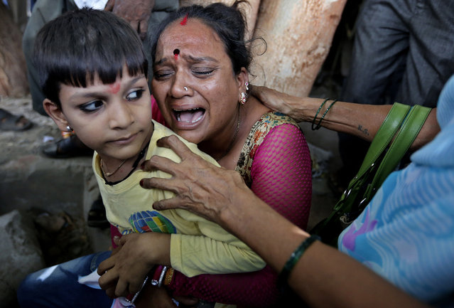 A relative of a an Indian man convicted for the 2002 Gujarat riots cries after the court announced the lengths of the sentences in Ahmadabad, India, Friday, June 17, 2016. An Indian court has sentenced 11 people to life in prison for murder in one of the many deadly religious riots that swept across the western state of Gujarat in 2002, leaving more than 1,000 dead. Special Court Judge P. B. Desai on Friday rejected the demand for death penalty as the prosecution failed to prove charges of criminal conspiracy against the defendants. The judge also sentenced 12 defendants to seven years in prison and one to 10 years in prison in the case. (Photo by Ajit Solanki/AP Photo)