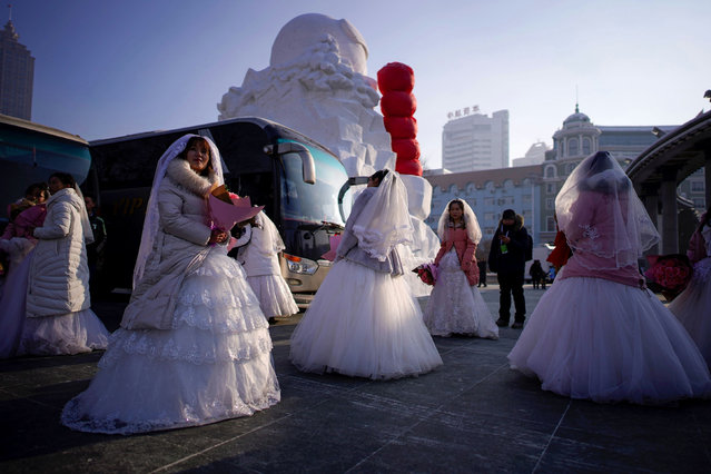 Newlywed couples attend their group wedding ceremony in frigid cold temperatures as part of the annual ice festival in the northern city of Harbin, Heilongjiang province, China on January 5, 2020. (Photo by Aly Song/Reuters)