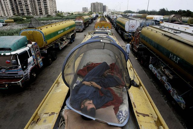 A man takes a nap on an oil tanker used to transport NATO fuel supplies to neighboring Afghanistan, in Karachi, Pakistan on May 17, 2012