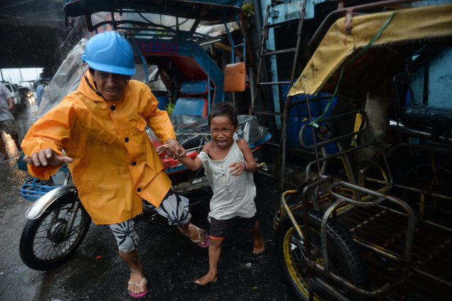 A village official leads a child as he is evacuated from their house at an informal settlers' area as Typhoon Rammasun barrels across Manila on July 16, 2014. Typhoon Rammasun shut down the Philippine capital on July 16 as authorities said the first major storm of the country's brutal rainy season claimed at least one life and forced hundreds of thousands to evacuate. (Photo by Ted Aljibe/AFP Photo)